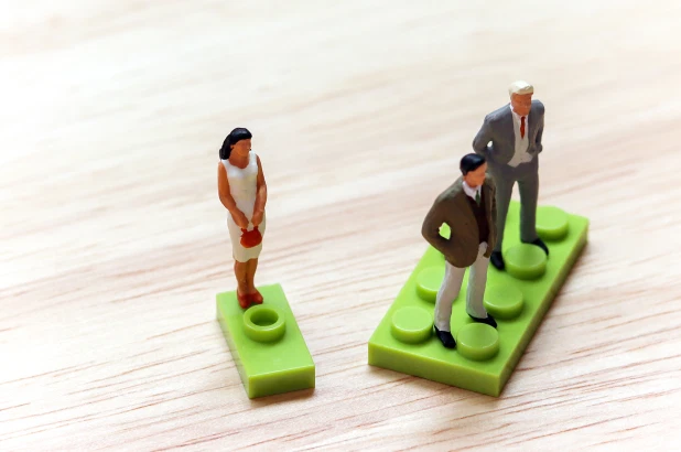 The image is a picture of toy people standing on lego pieces against a wooden background. Two toy men are standing together confidently on a large lego piece, while a woman stands alone on the edge of a tiny lego piece. Source: https://nypost.com/2020/03/05/9-out-of-10-people-are-biased-against-women-global-study/